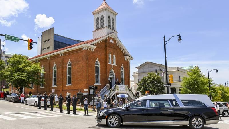 The body of Congressman John Lewis passes Dexter Avenue King Memorial Baptist Church on the way...