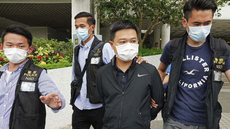 Ryan Law, second from right, Apple Daily's chief editor, is arrested by police officers in Hong...