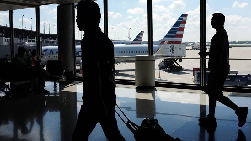 FILE - In this Aug. 1, 2016 file photo, passengers walk to their gates through the terminal as...