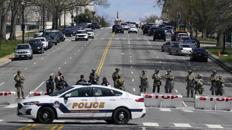 Officials respond at the scene of a car that crashed into a barrier on Capitol Hill in...