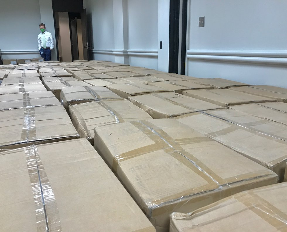 State Superintendent Dr. Eric Mackey looks at the boxes of PPE about to be sent out to schools...