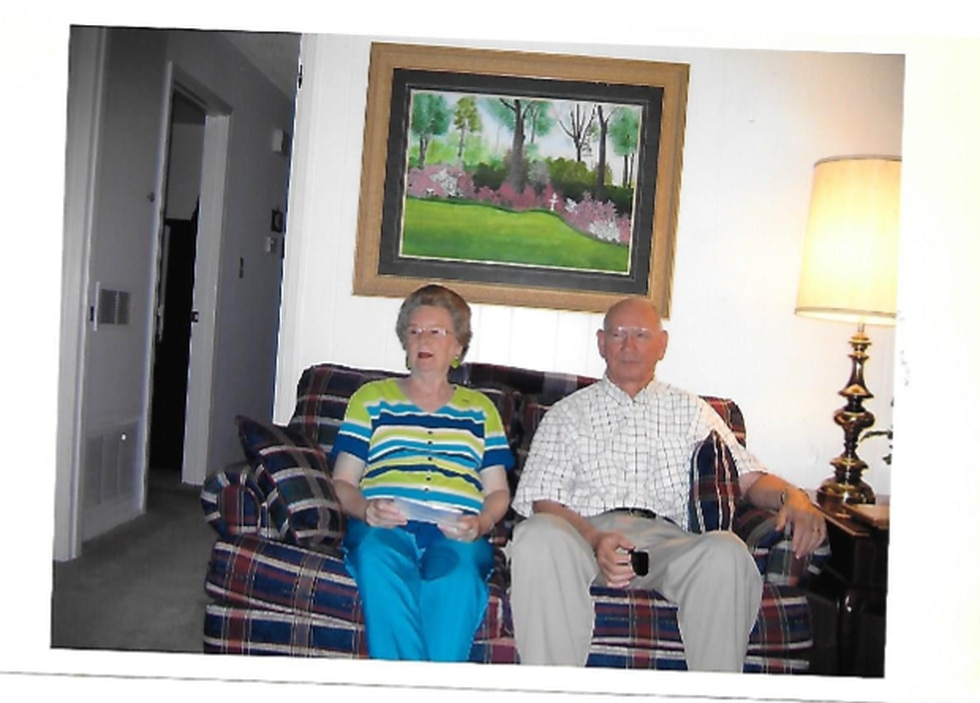 Mr. and Mrs. Roberson relax on the couch at the Greenville home they've shared for nearly...