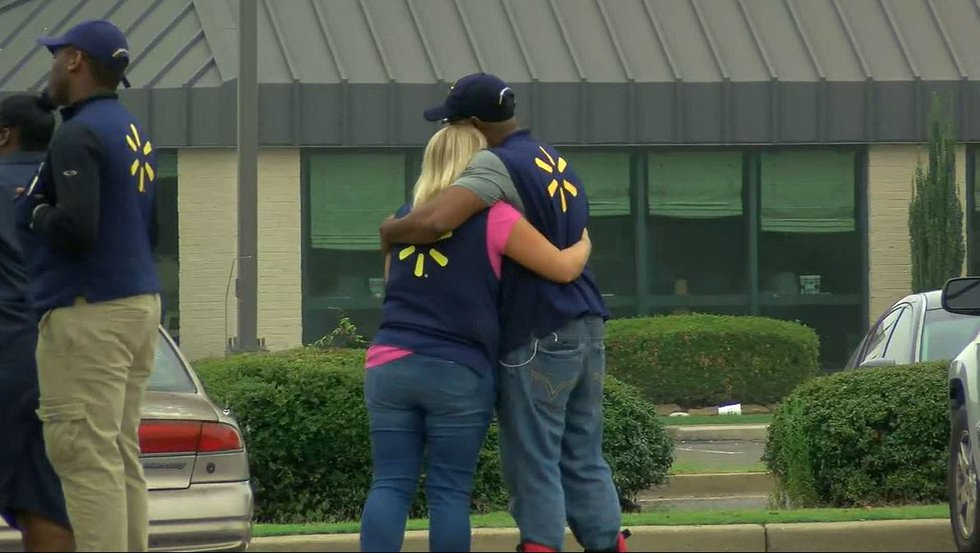 Walmart employees in Southaven embrace after two of their coworkers were shot and killed July...