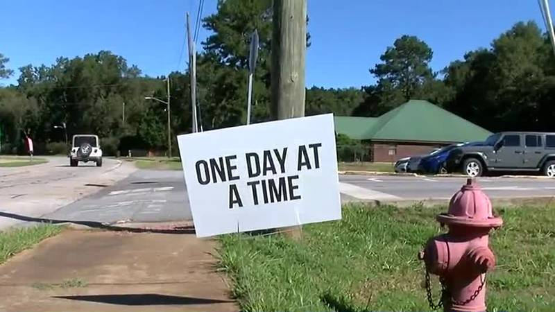 Family places encouraging signs outside Harris County schools for suicide prevention awareness