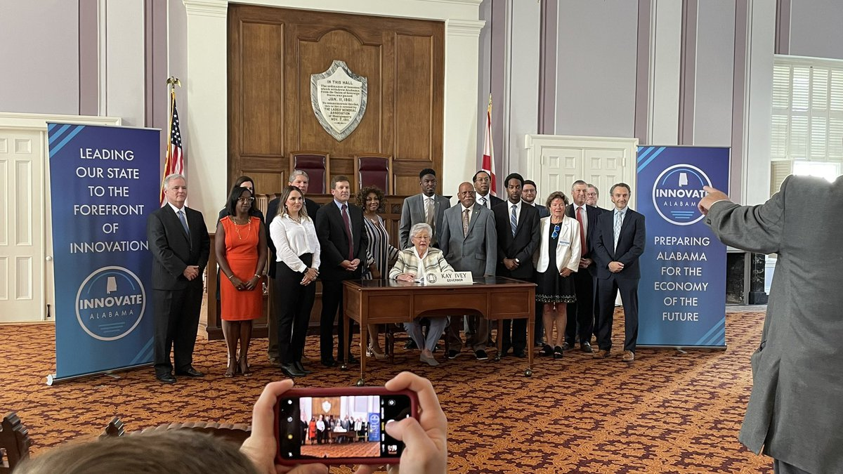 Legislators pose for a picture with Gov. Kay Ivey during a ceremonial bill signing on July 29,...