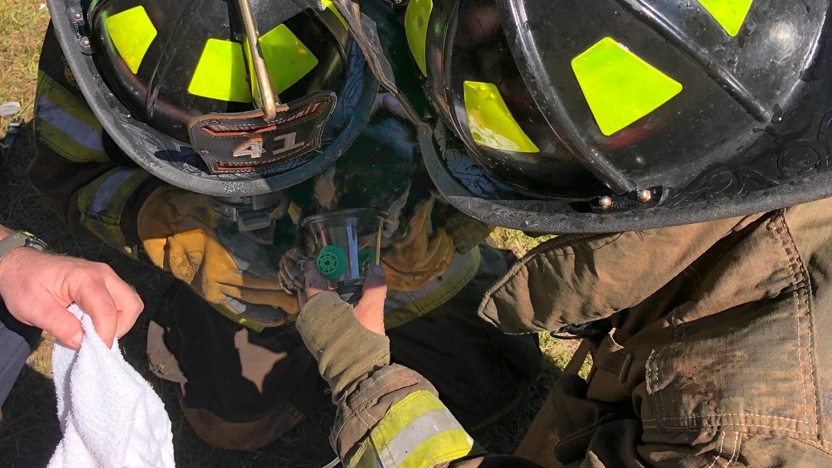 Troup Co. firefighters treat dog after rescuing it from burning structure.