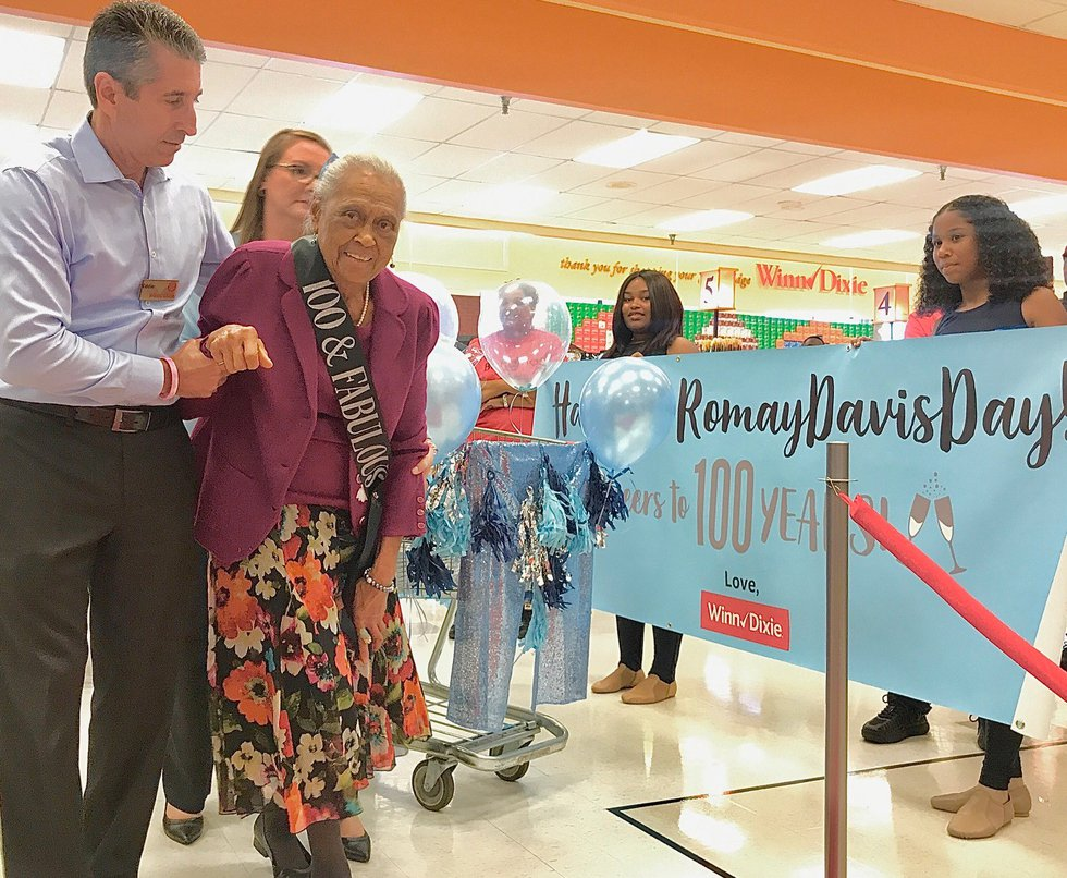 Winn Dixie managers escort Romay Davis to her seat at the end of a red carpet. There, she was...